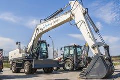 新的挖掘机在路在城市,与蓝天的一个晴天 免版税库存图片