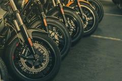 新的摩托车前轮特写镜头  在柏油路停放的大自行车 有体育设计的偶象摩托车 黑色轮胎 免版税库存图片