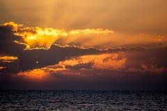 新的日 海洋与打破在云彩后的太阳的黎明天际 库存照片