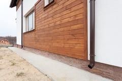 新的棕色铜天沟在有白色墙壁和木板条的房子里 图库摄影