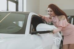 新的汽车的年轻女实业家购物在经销权陈列室 库存图片