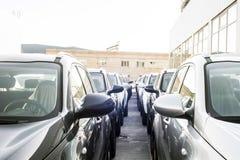 新的汽车行停放在车商商店 免版税库存照片