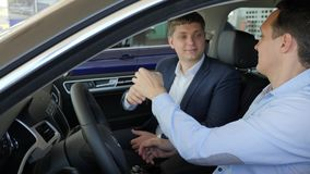 新的汽车,专业推销员销售汽车客户,在车陈列室,汽车经销商的好成交发送密钥  股票视频