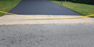 新的沥青车道和黄色小心磁带 免版税库存照片