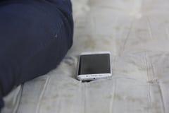 新的流动手机在沙发离开在腿附近 库存照片