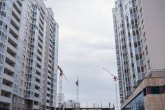 新的灰色多层的住宅房子和三台建筑用起重机 免版税图库摄影