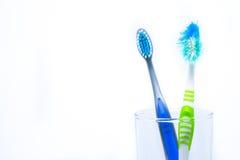 新的牙刷和老牙刷在t的清楚的玻璃损坏了 免版税库存照片