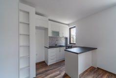 新的现代和空的白色厨房 家庭新 内部摄影 木的楼层 免版税库存图片