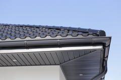 新的现代房子的角落有天沟、屋顶、墙壁和灯的 库存照片