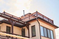 新的现代生态村庄房子上面特写镜头细节与盖的棕色屋顶的在天空蔚蓝背景 图库摄影