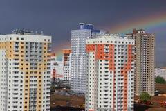 新的现代黑暗的天空背景的块多层的房子在四种颜色:红色,橙色,灰色和白色 恶劣天气和彩虹 Bui 免版税库存图片