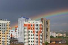 新的现代黑暗的天空背景的块多层的房子在四种颜色:红色,橙色,灰色和白色 恶劣天气和彩虹 Bui 库存照片