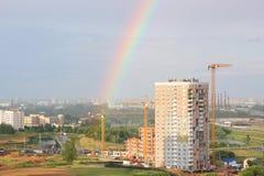 新的现代黑暗的天空背景的块多层的房子在四种颜色:红色,橙色,灰色和白色 恶劣天气和彩虹 Bui 免版税库存照片