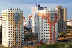 新的现代深蓝天空背景的块多层的房子在四种颜色:红色,橙色,灰色和白色 新大厦的房子 mort 免版税图库摄影