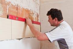 新的瓦片行在家庭厨房里 铺磁砖工在工作 免版税库存图片