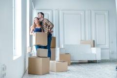 新的生活 在移动的爱的夫妇和在他的手保留一个箱子和 免版税库存图片