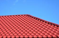 新的红色金属铺磁砖了屋顶房子屋顶建筑外部 免版税库存照片