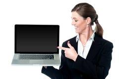 介绍新的膝上型计算机的女性销售主管 库存照片