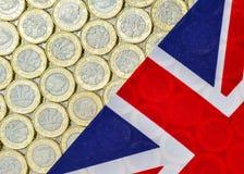 新的英国一1英镑硬币和英国旗子 免版税图库摄影