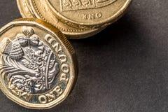 新的英国在黑暗的背景的一个纯正的1英镑硬币 免版税库存照片