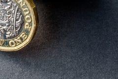 新的英国在黑暗的背景的一个纯正的1英镑硬币 库存图片