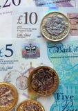 新的英国塑料钞票和1英镑硬币 库存图片