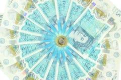 新的英国聚合物五磅笔记和新12支持£1硬币 免版税库存照片