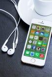 新的苹果计算机在金子颜色的Iphone 5s与耳机。 免版税图库摄影