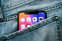 新的苹果计算机iPhone x 10在牛仔布牛仔裤长裤的口袋 免版税图库摄影
