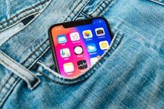 新的苹果计算机iPhone x 10在牛仔布牛仔裤长裤的口袋 免版税库存照片