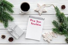 新的解决方法年 在圣诞节玩具中的笔记本和在白色木背景顶视图的云杉的分支 免版税图库摄影