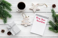 新的解决方法年 在圣诞节玩具中的笔记本和在白色木背景顶视图的云杉的分支 免版税库存照片