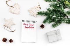 新的解决方法年 在圣诞节玩具中的笔记本和在白色背景顶视图的云杉的分支 免版税图库摄影