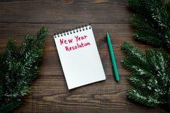 新的解决方法年 在黑暗的木背景顶视图的笔记本整洁的云杉的分支 图库摄影