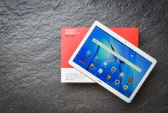 新的计算机片剂华为mediapad t3与显示家庭屏幕前面华为商标的10英寸白色在包裹箱子 免版税库存图片