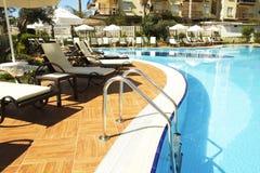 新的豪华住宅复合体游泳池区域与瓦片、镀铬物台阶把柄和流失的 晴朗的美好的天 免版税库存图片