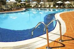新的豪华住宅复合体游泳池区域与瓦片、镀铬物台阶把柄和流失的 晴朗的美好的天 免版税库存照片