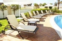 新的豪华住宅复合体游泳池区域与瓦片、镀铬物台阶把柄和流失的 晴朗的美好的天 图库摄影