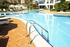 新的豪华住宅复合体游泳池区域与瓦片、镀铬物台阶把柄和流失的 晴朗的美好的天 库存照片