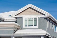新的豪华住宅房子上面雪的在冬天好日子 免版税库存图片