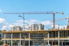 新的购物中心或购物中心建造场所在有起重机的机械,脚手架城市,具体与钢增强 免版税库存照片