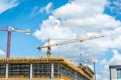 新的购物中心或购物中心建造场所在有起重机的机械,脚手架城市,具体与钢增强 库存图片