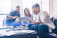 介绍新的起始的项目的概念 小组年轻工友谈论想法互相在现代办公室 免版税库存照片