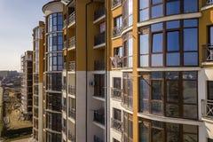 新的高公寓和停放的汽车和郊区房子天空蔚蓝拷贝空间背景的 免版税库存照片