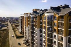 新的高公寓和停放的汽车和郊区房子天空蔚蓝拷贝空间背景的 库存照片