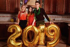 新的2019年来临 运载金子的小组快乐的年轻人上色了数字并且获得乐趣在党 免版税库存照片