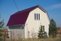 新的建造的乡间别墅有红色屋顶的和盖用米黄房屋板壁 免版税库存照片