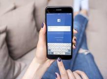 新的黑iPhone与社会网络Facebook的7个加号在手上 免版税库存照片