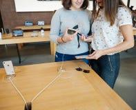 新的iPhone 8和iPhone 8个加号在有女孩买的苹果计算机商店 图库摄影