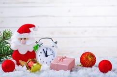 新的Year& x27; s构成:圣诞老人、时钟和礼物在白色雪复制 库存照片